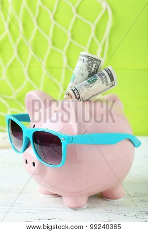 Pink Piggy Bank With Dollars On White Wooden Background