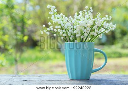 Lily Of The Valley In Cup On Grey Wooden Background, Outdoors