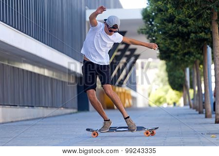 Handsome Young Man Skateboarding In The Street.