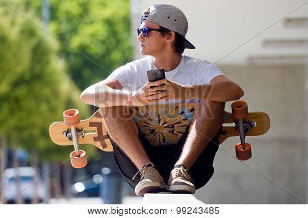 Handsome Skater Boy Using His Mobile Phone In The Street.