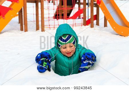 little boy having fun in winter playground