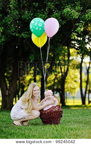 Mother With Little Girl On Background Of Green Trees. Baby Girl Sitting In A Basket With Balloons