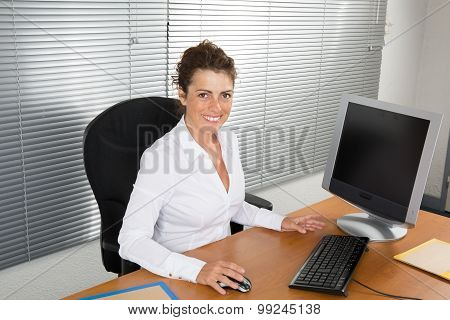 Businesswoman Sitting At Desk And Working. Smiling And Looking Back At Camera
