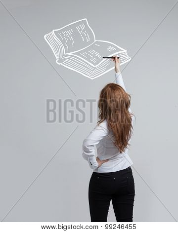 young woman drawing a book