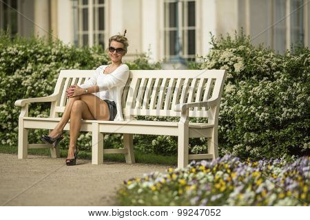 Young attractive blond woman sitting on a bench in the garden.