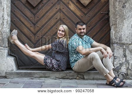 Young married couple sitting on the stone threshold of the old house.
