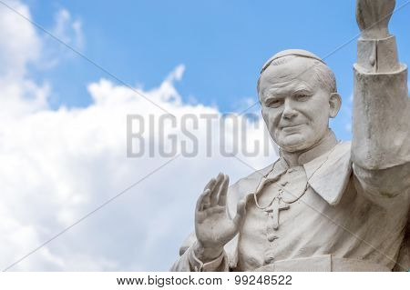 Statue Of Pope John Paul Ii Blessing People, With Cloudy Sky In The Background
