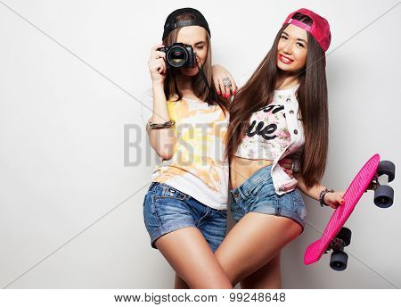 Beautiful young women in summer clothes holding pink skateboard and take picture while standing against grey background