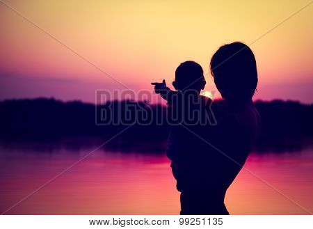 Silhouettes of Father and Baby Watching Sunset