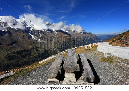 Snow-capped Alps in beautiful autumn day. Table and benches for picnic on the side of the  road. Great highway winds between hillsides yellowed