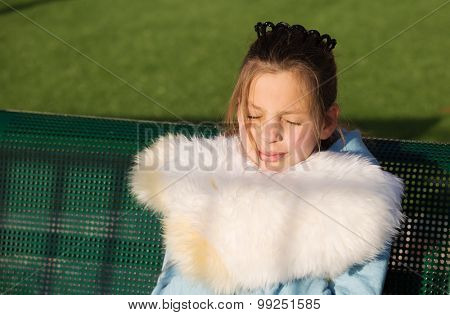 Beautiful teenage girl smiles in the sun, wrapped in a great fur. Family children's party