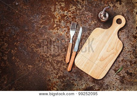 Cutting boards, knife and fork on a rustic background