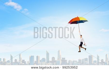 Young businesswoman flying high in sky on umbrella