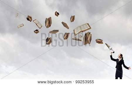 Young businesswoman screaming in megaphone and books flying out