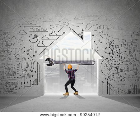 Young engineer woman lifting big wrench key above head