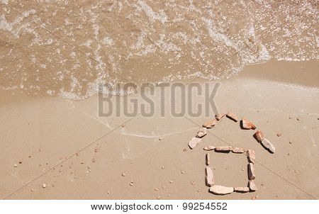 little house drawn in the sand of sea beach