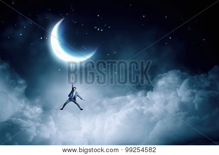 Young businessman hanging on rope at night