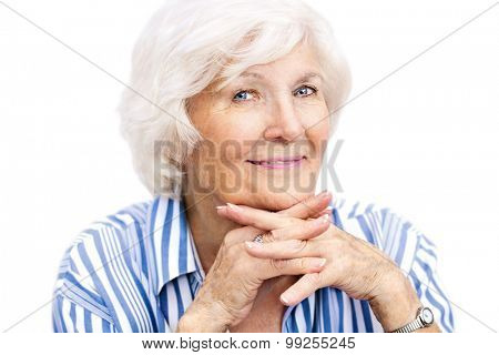 Senior lady looking relaxed at camera with interlaced fingers