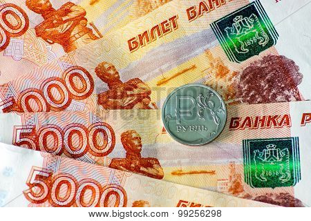 one ruble coin and five thousand rubles banknotes