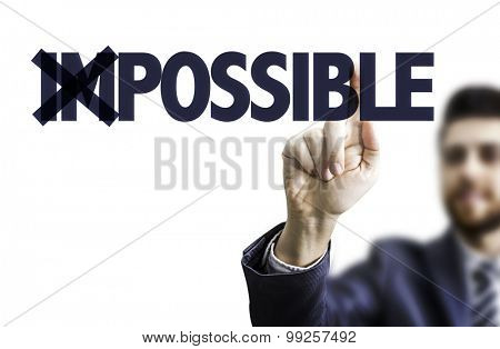 Business man pointing the text: Impossible/Possible