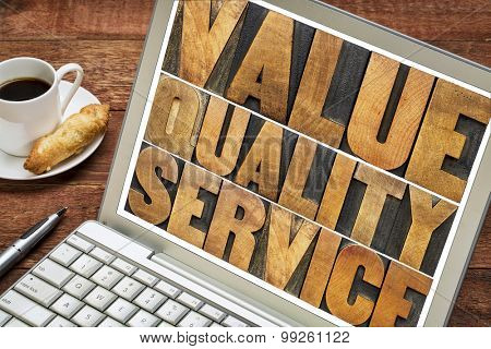value, quality, service - business mantra or motto concept - words in vintage letterpress wood type on a laptop screen with a cup of coffee