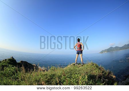 young fitness woman trail runner enjoy the view on seaside mountain