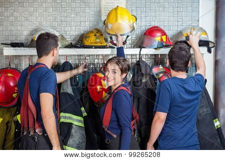 Male and female firefighters getting ready in fire station