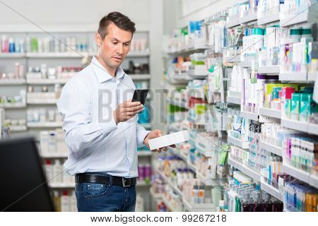 Mid adult male consumer checking information on mobile phone while holding product in pharmacy