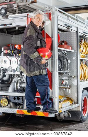 Full length portrait of smiling fireman standing on truck at fire station