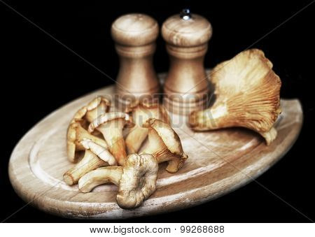 chanterelle mushrooms on the wooden cutting board against black background