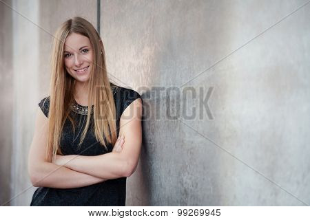 Attractive teenage girl standing next to concrete wall