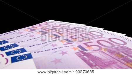 Various 500 euro notes isolated on black background