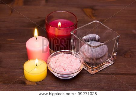 Candles and bath salts on wood