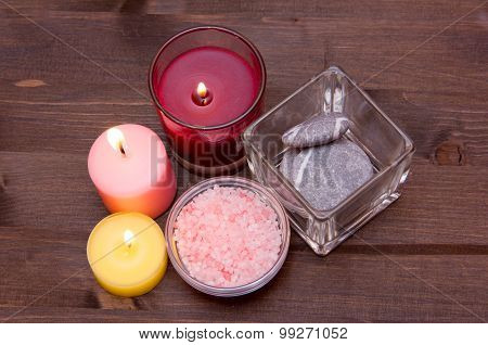 Candles and bath salts on wood from above