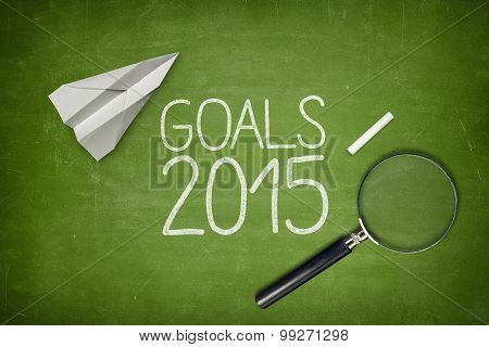Goals 2015 concept on green blackboard with empty paper sheet