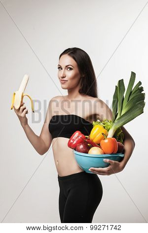 Portrait Of Young Fit Woman Holding Fruits And Vegetables