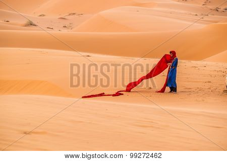 MERZOUGA, MOROCCO, APRIL 13, 2015: Local man arranges his turban on sand dunes of Erg Chebbi