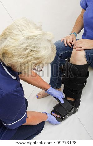 Nurse Fitting an Orthopaedic Boot to a Lady with a Broken Leg