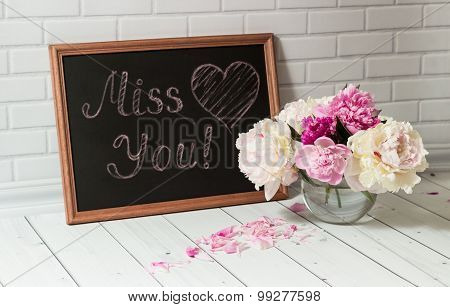 Chalkboard with inscription Miss You and peonies