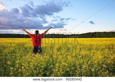 Farmer with outstretched arm at the rape field. Beautiful landscape with field of yellow canola (Brassica napus L.) and blue sky