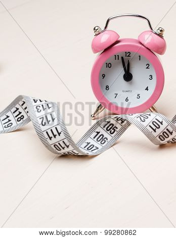 Pink Alarm Clock And Measuring Tape