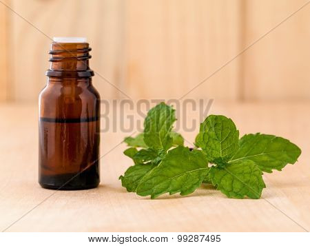 Bottle Of Mint Essential Oil On Wooden Background With Selective Focus.