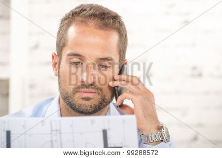 A Young Man Reads A Plan And Phone