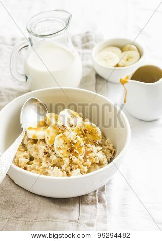 Oatmeal With Banana, Caramel Sauce And Pecan Nuts In A White Bowl On A Light Surface, A Delicious An