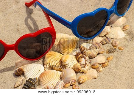 Heap Of Shells And Sunglasses On Sand At The Beach