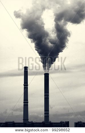 Grey smoking industrial two chimneys