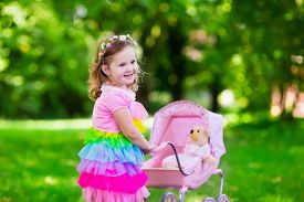 picture of baby doll  - Little girl pushing toy stroller with bear - JPG