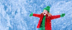 foto of snow forest  - Little girl in red jacket and green knitted hat catching snowflakes in winter park on Christmas eve - JPG