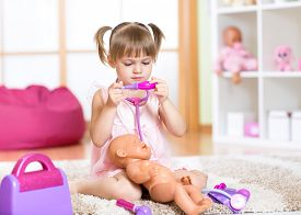 image of baby doll  - Child girl playing the doctor with her newborn baby doll in room  - JPG