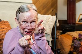 picture of matron  - Funny old woman in pink sweater showing dance style hand gesture - JPG
